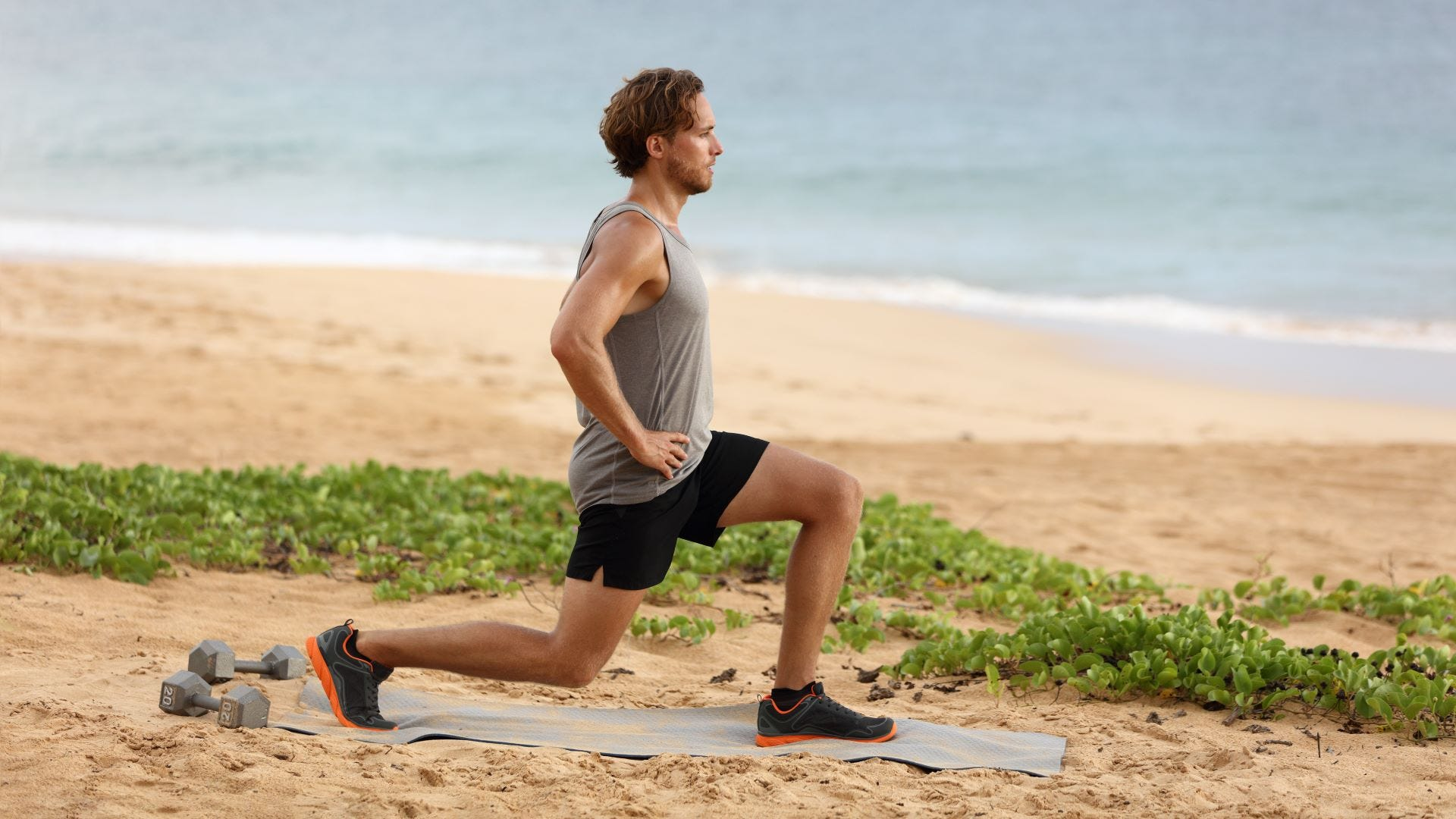 A man doing lunges on a beach.