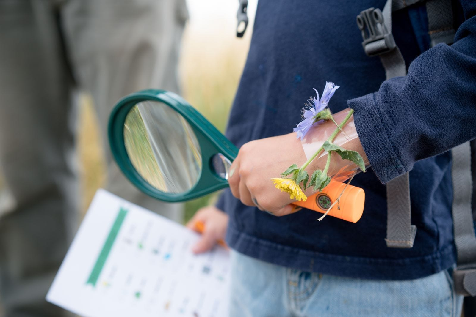 A child holding a magnifying glass and a list for a scavenger hunt.