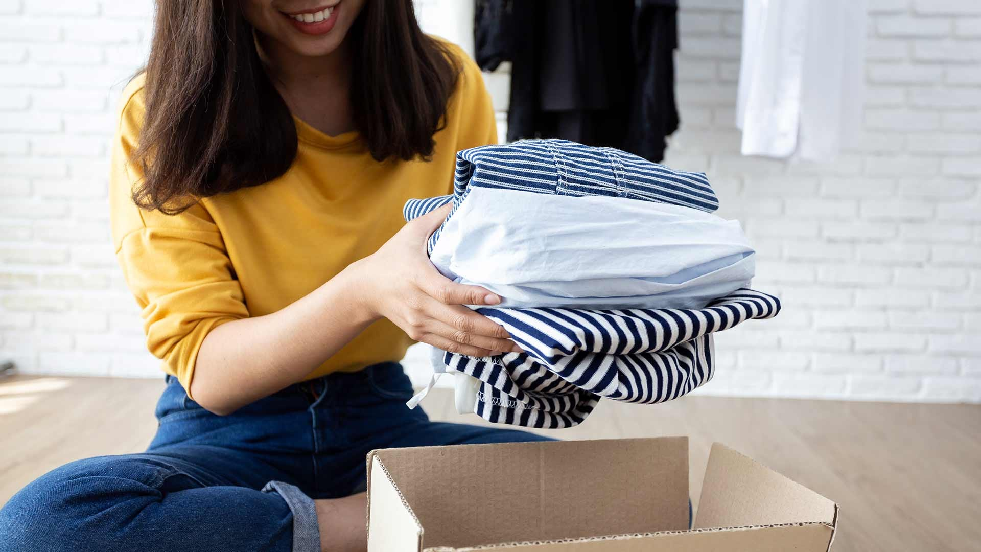 A woman cleaning out her closet and packing up clothing to donate.