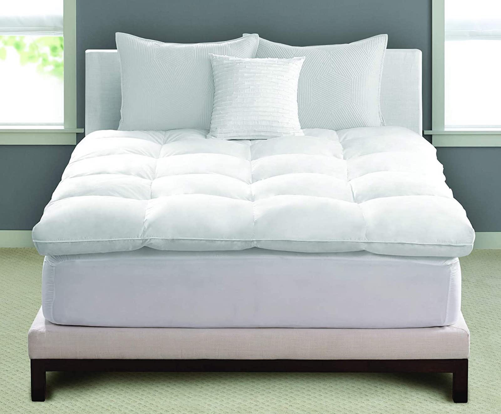 A bed with a white, fluffy mattress topper and three white pillows