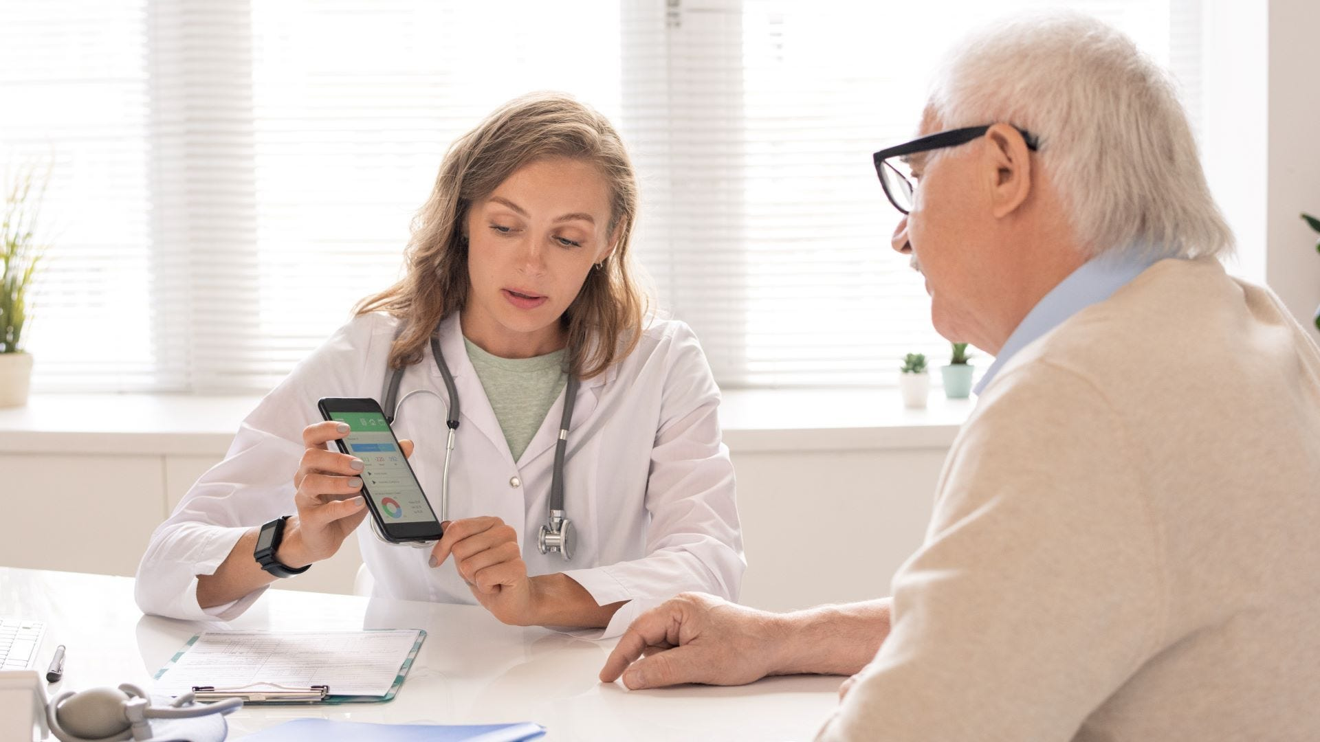 A doctor showing a patient something on his phone.
