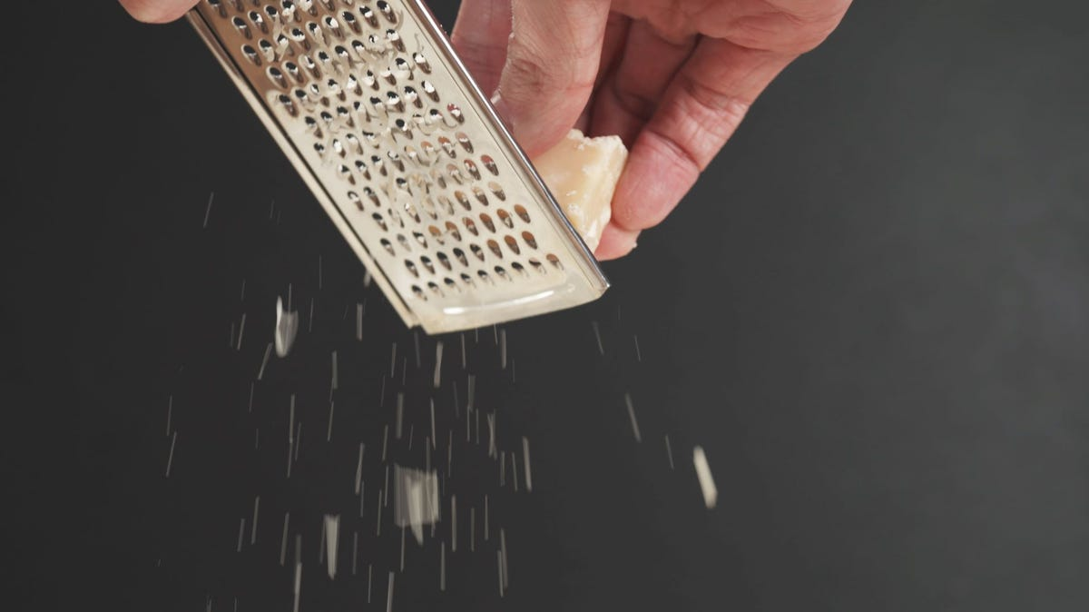 Someone grating a block of Parmesan cheese.