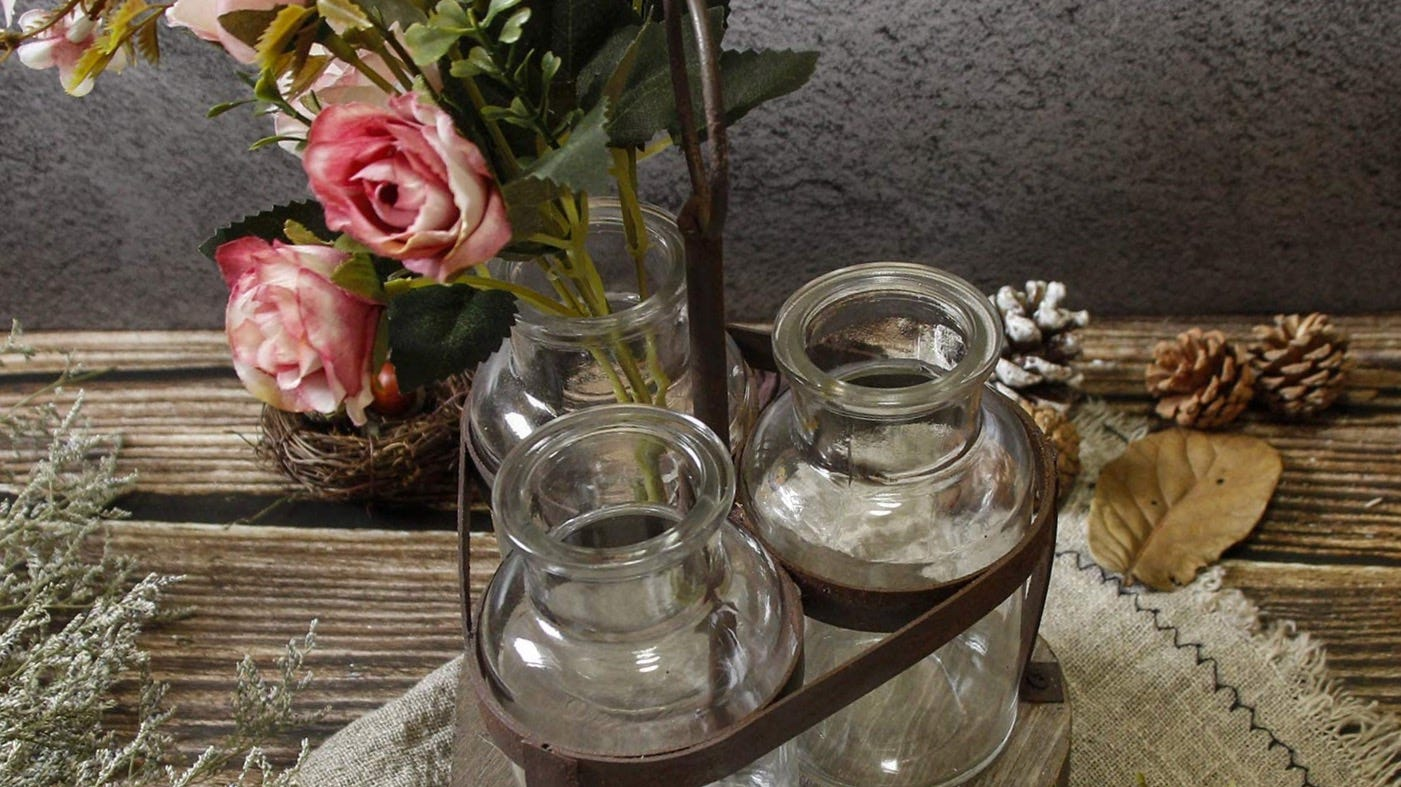 Three vases in a wood and metal stand on a table.