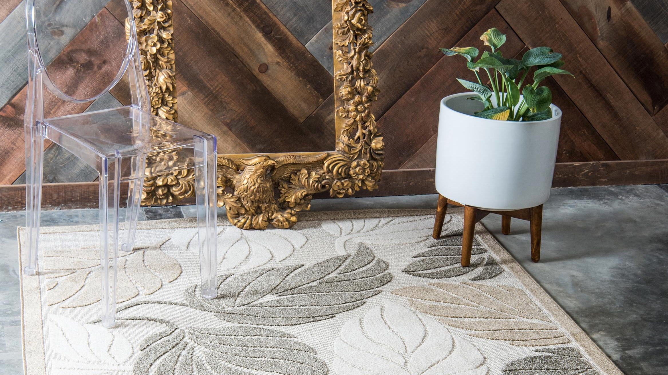 A leaf-print rug under a potted plant, chair, and wall mirror.
