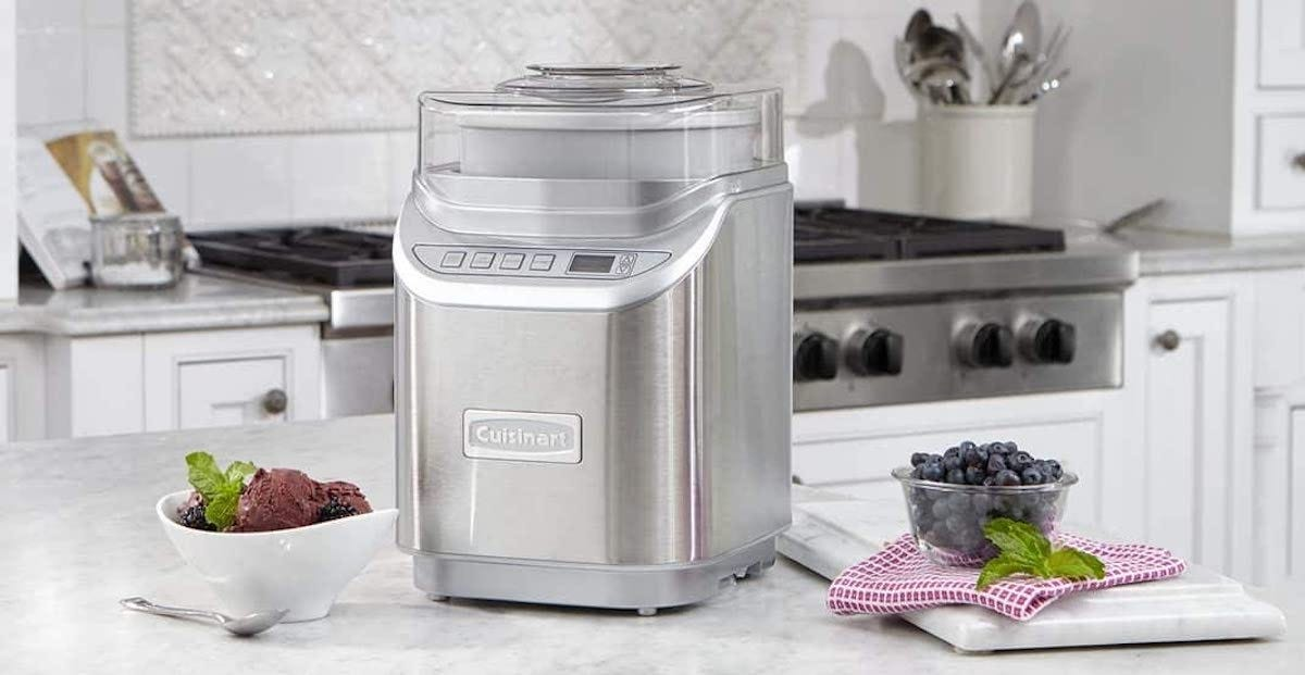 The Cuisinart ice cream maker on a counter with a bowl of ice cream and a bowl of blueberries sitting next to it.