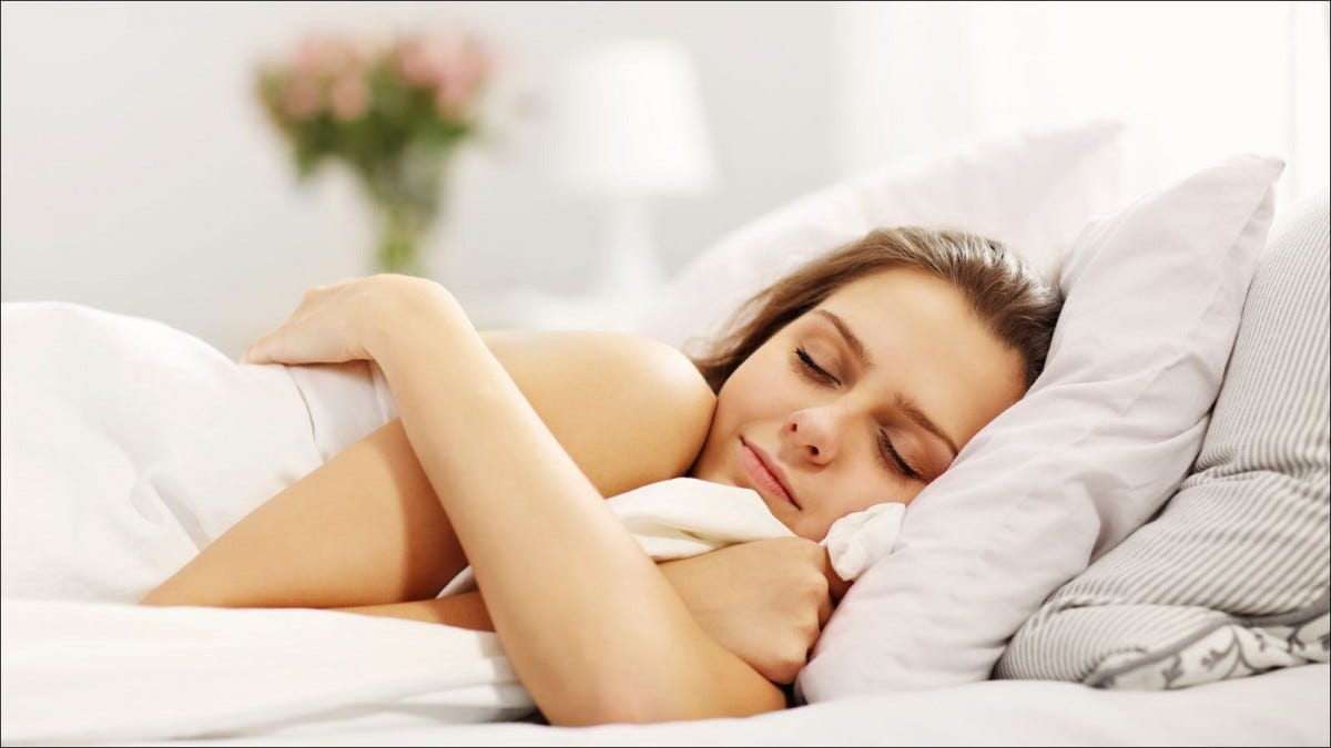 A woman sleeps in white bedding.