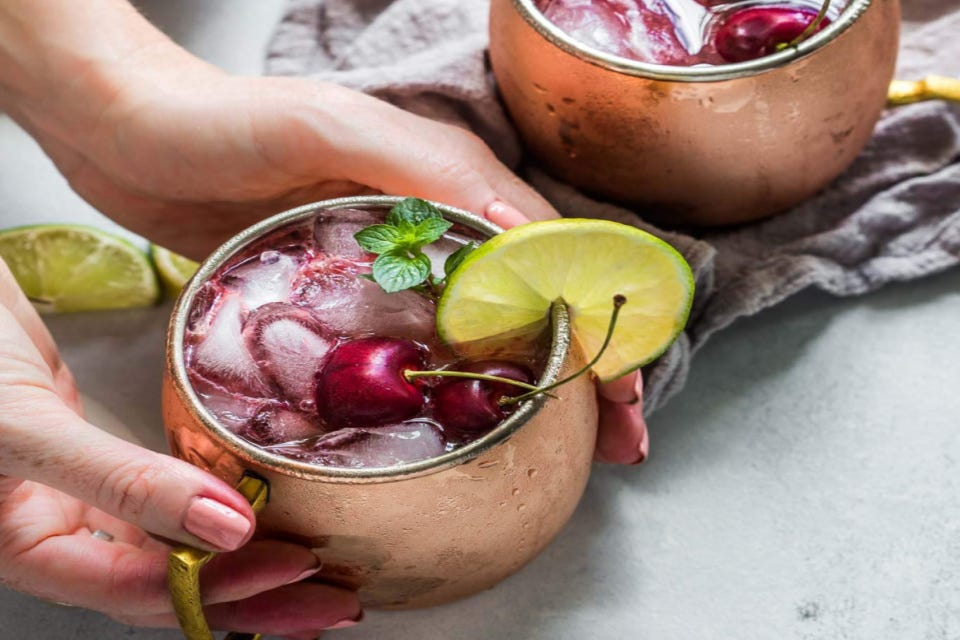 Someone holding a copper mug filled with a cherry Moscow Mule cocktail garnished with lime, fresh cherries, and mint leaves.