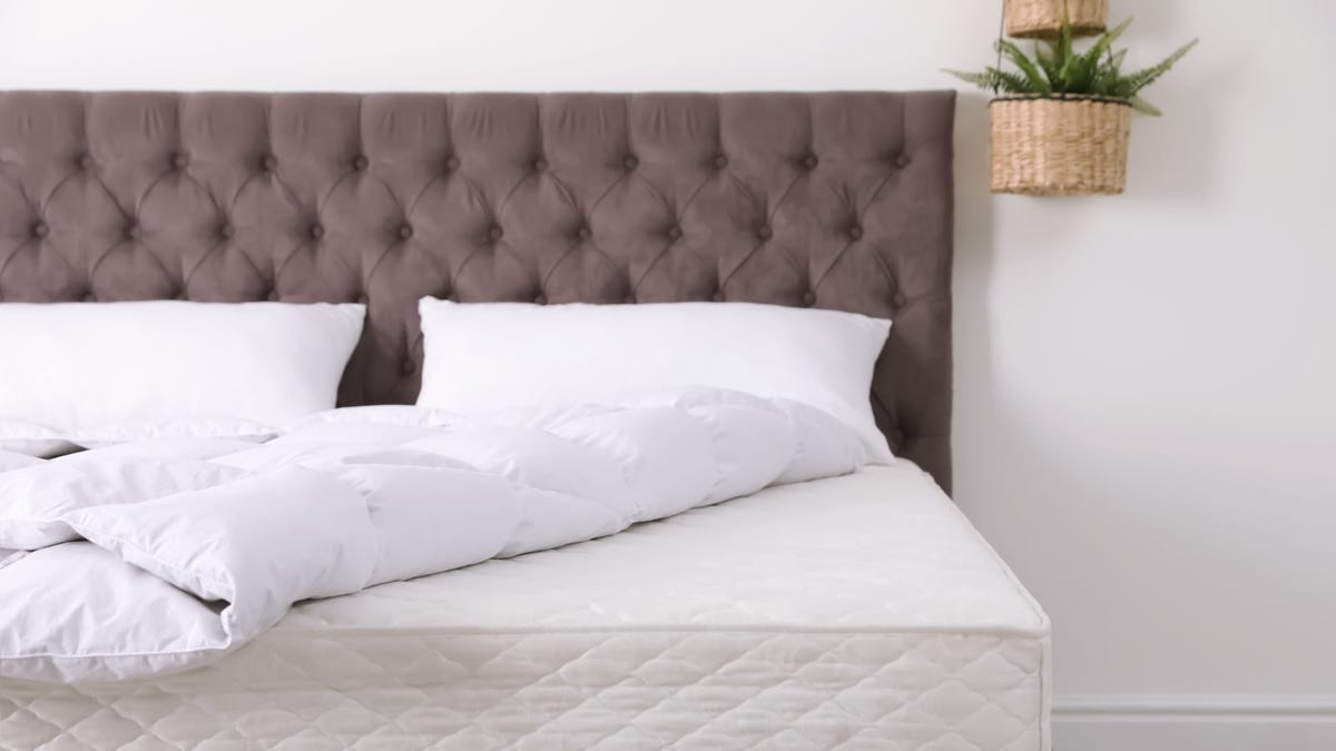 A mattress on a platform bed with a white down comforter.
