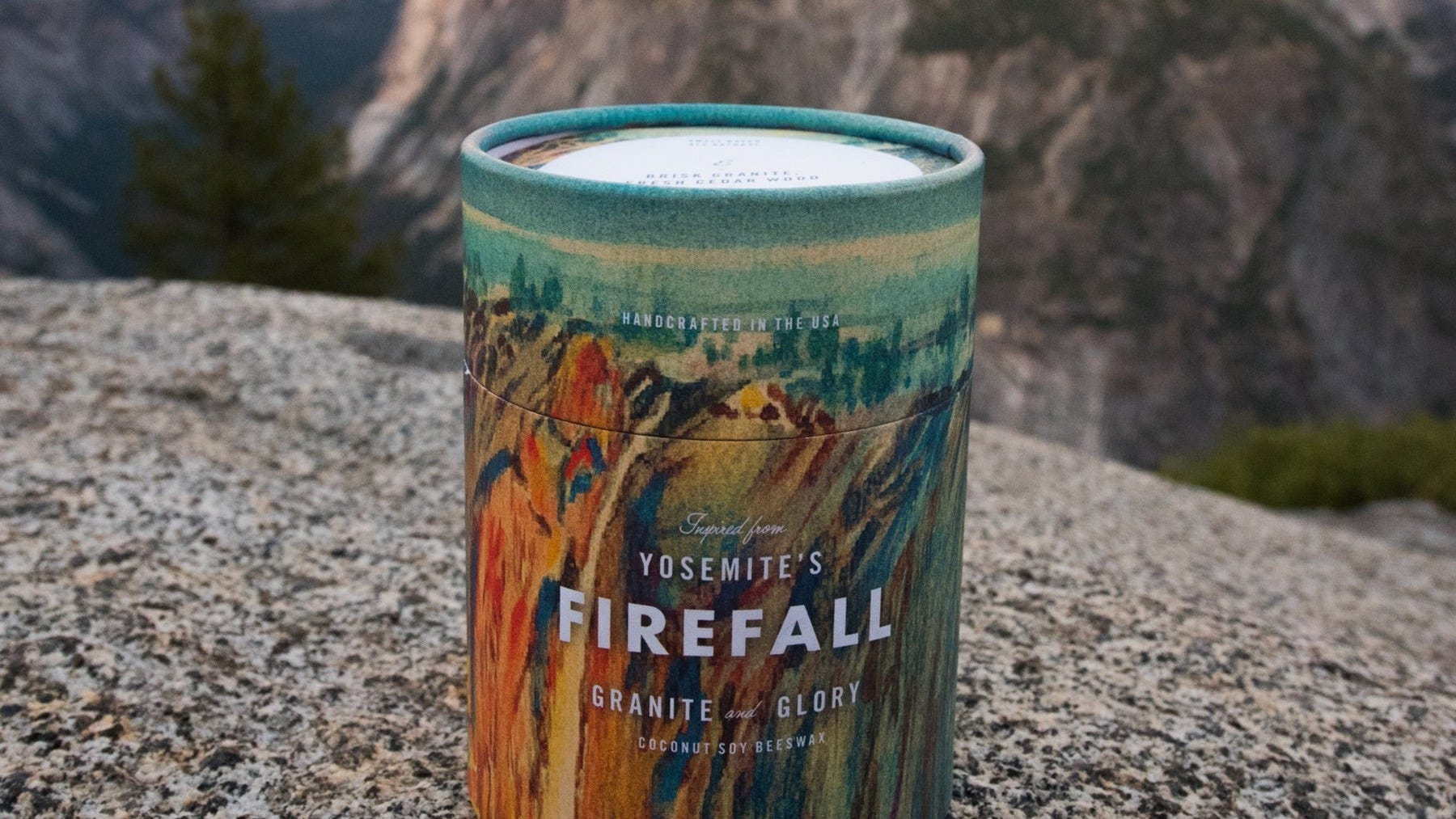 A candle in cardboard tube packaging with a scene of mountains in the distance.