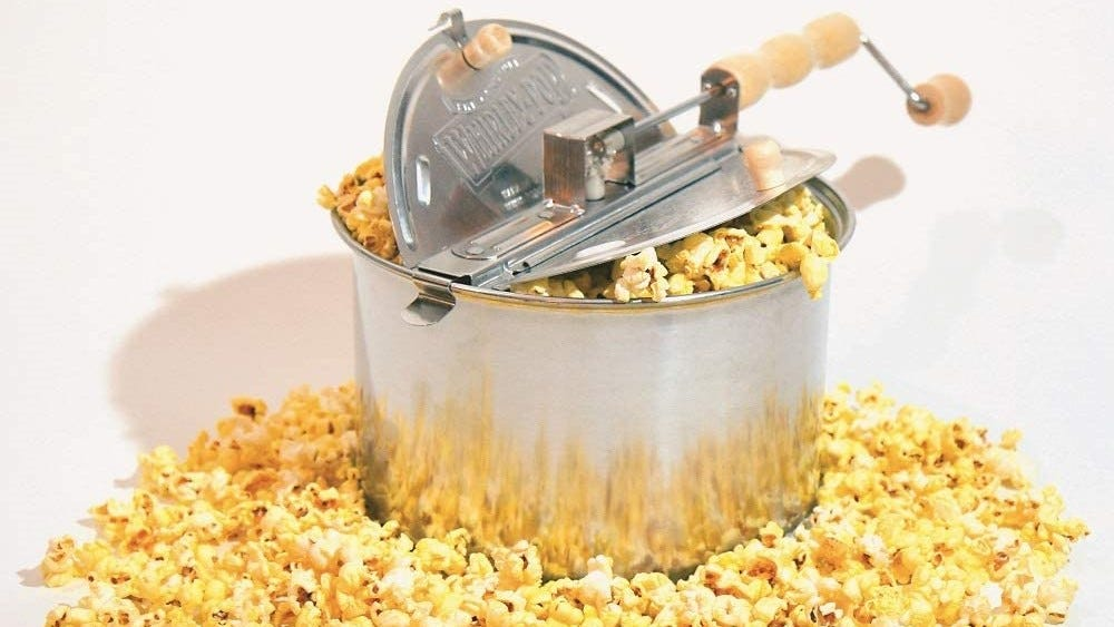 Whirley-Pop popcorn maker overflowing with popcorn.