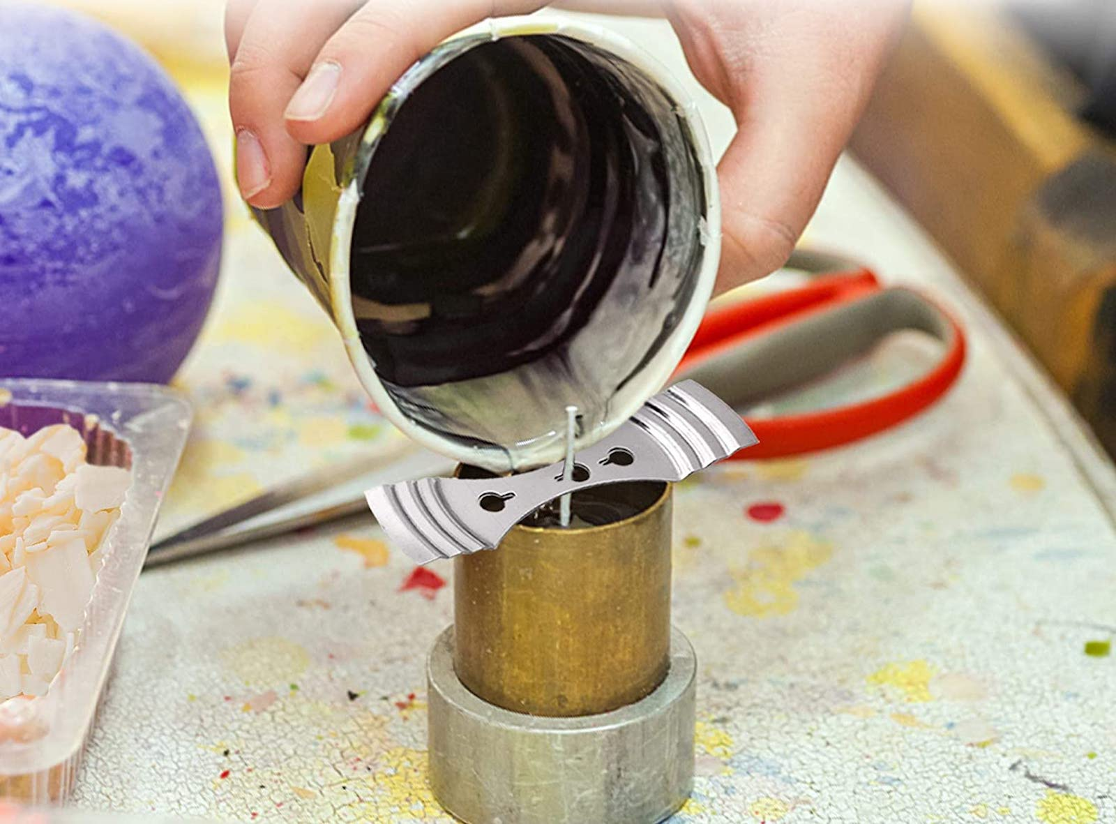 A hand pouring wax into a candle mold with a wick held steady by a piece of metal