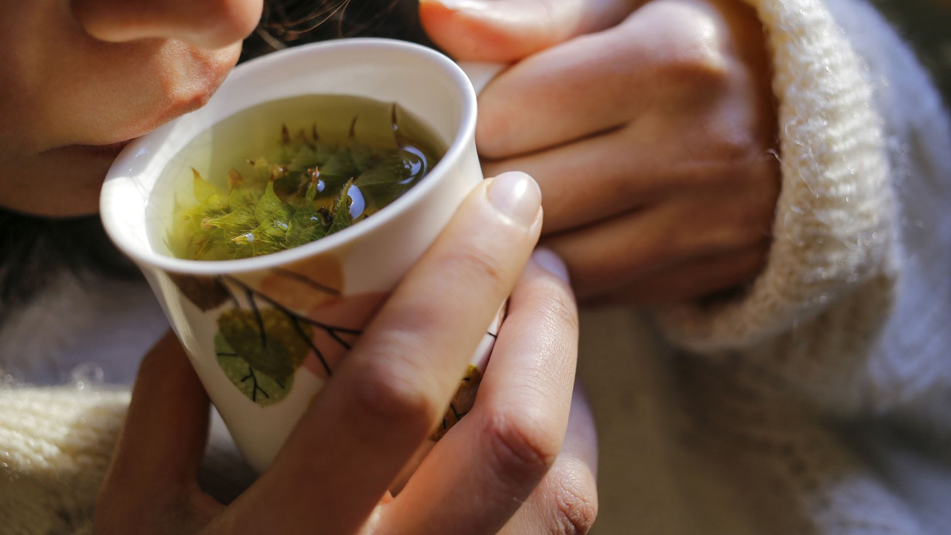Woman drinking a mug of sage tea.