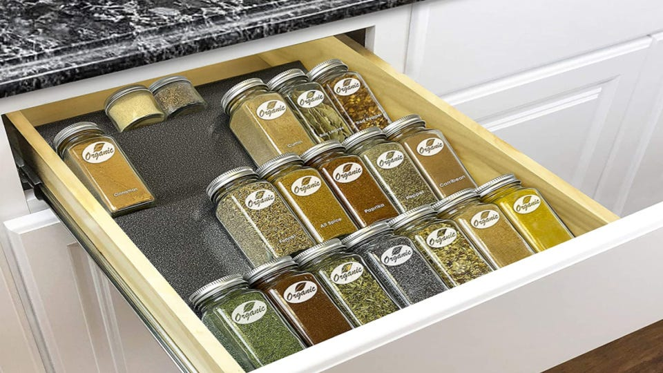 Multiple spice jars neatly organized on a rack in a drawer.