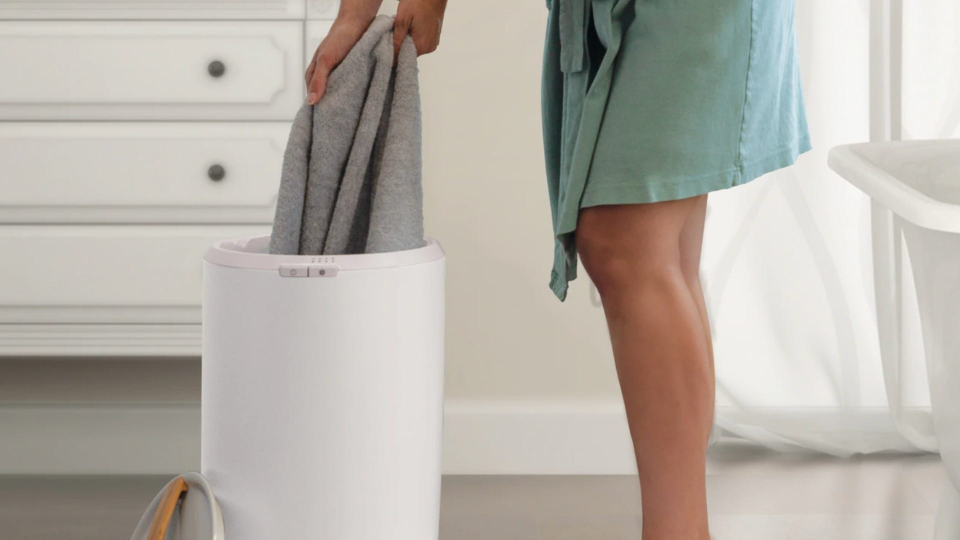 person pulling towel out of towel warming bin