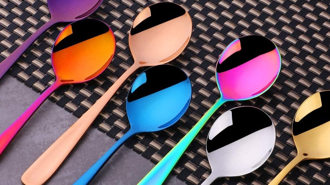 Seven rainbow stainless-steel spoons on a table.