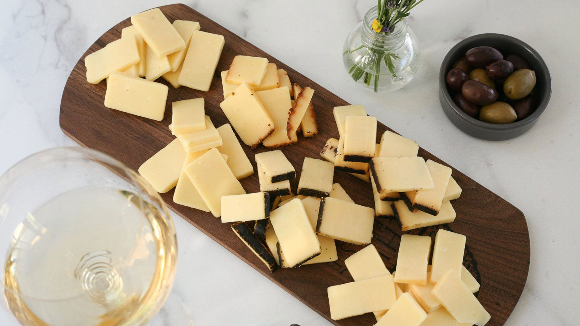 A cutting board covered with gourmet cheese.
