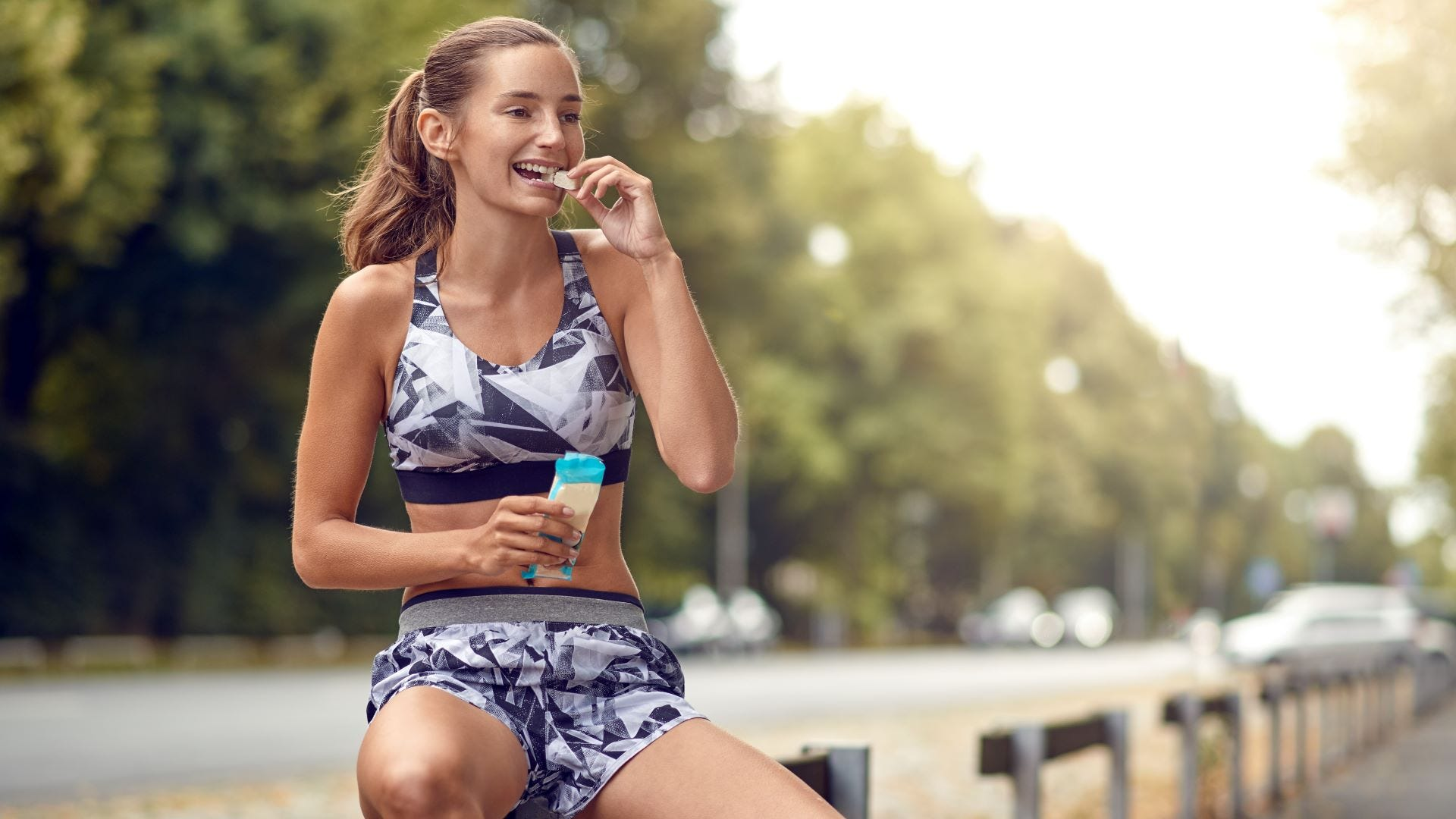 A woman in workout clothes eating a protein bar at a park.