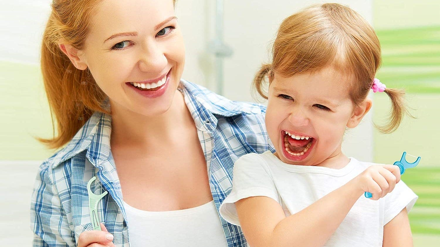 Mom and child using Plackers dental floss.