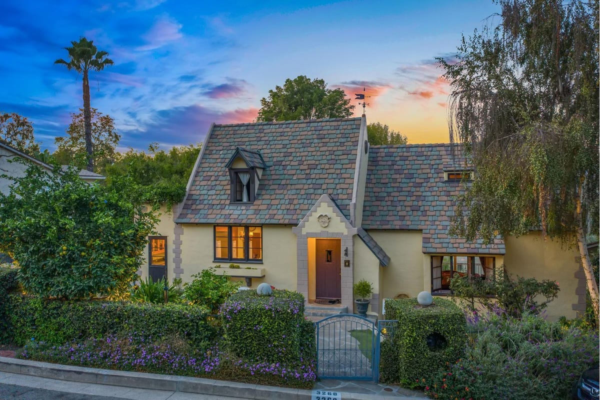 The sun sets behind a cottage inspired by a fairy tale.