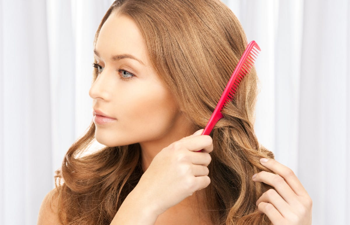 redheaded woman using a bright red comb on her hair