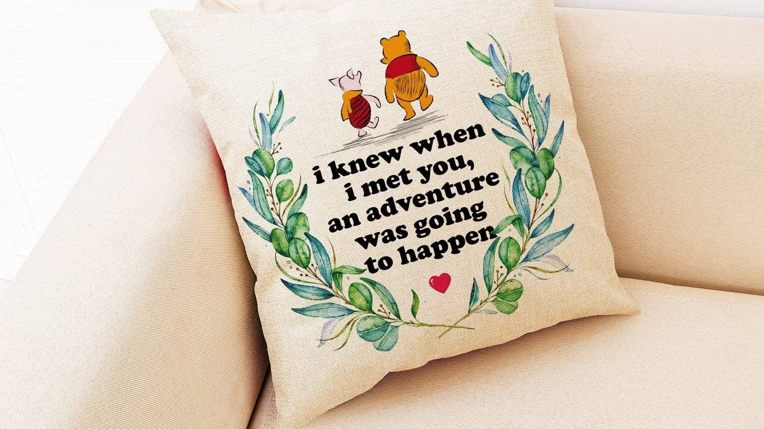 Winnie the Pooh and Piglet pillow on a couch.