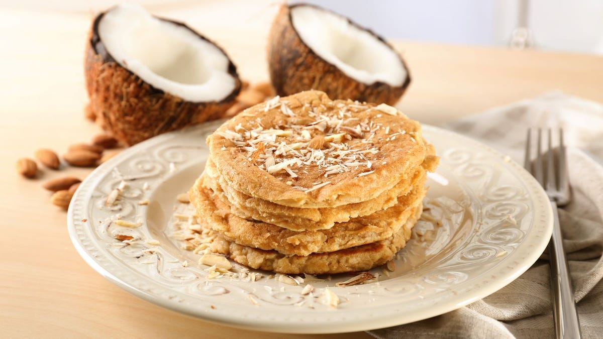 A stack of grain-free, coconut pancakes on a plate, next to two halves of a coconut.
