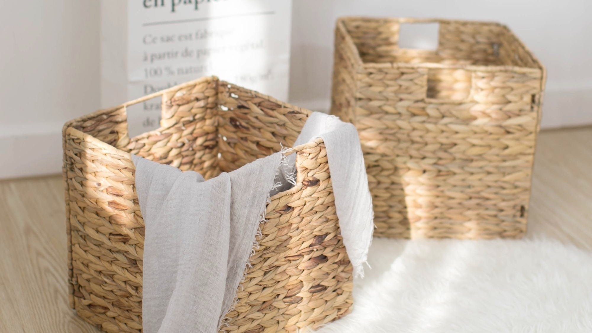 Two wicker storage baskets, one empty and one holding a blanket.
