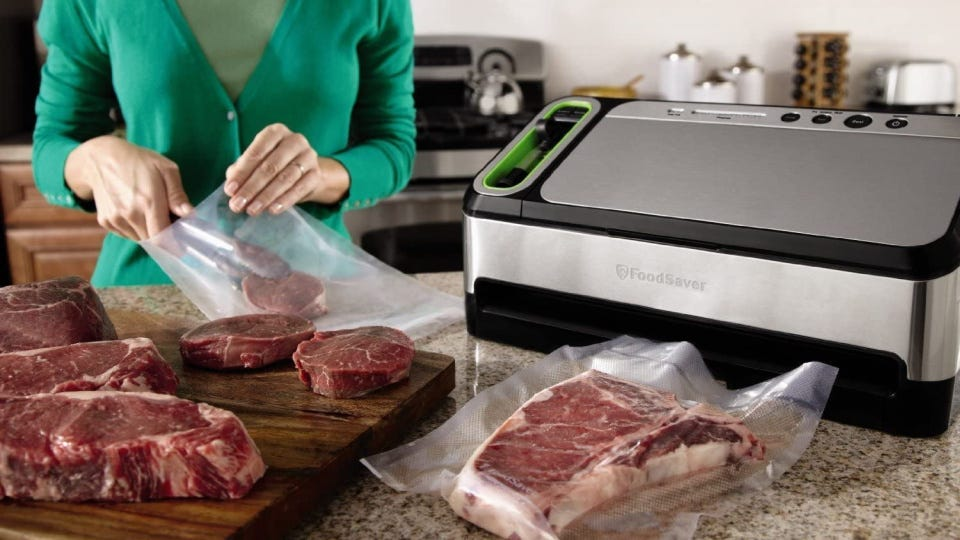 A women placing multiple cuts of beef in a food saver bag before sealing and storing them in the freezer.