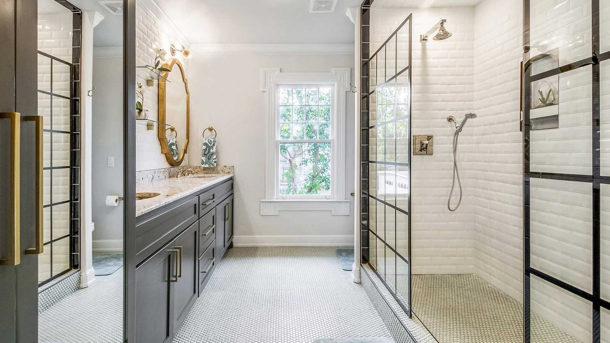 An upscale bathroom with a glass half-door on the shower stall.
