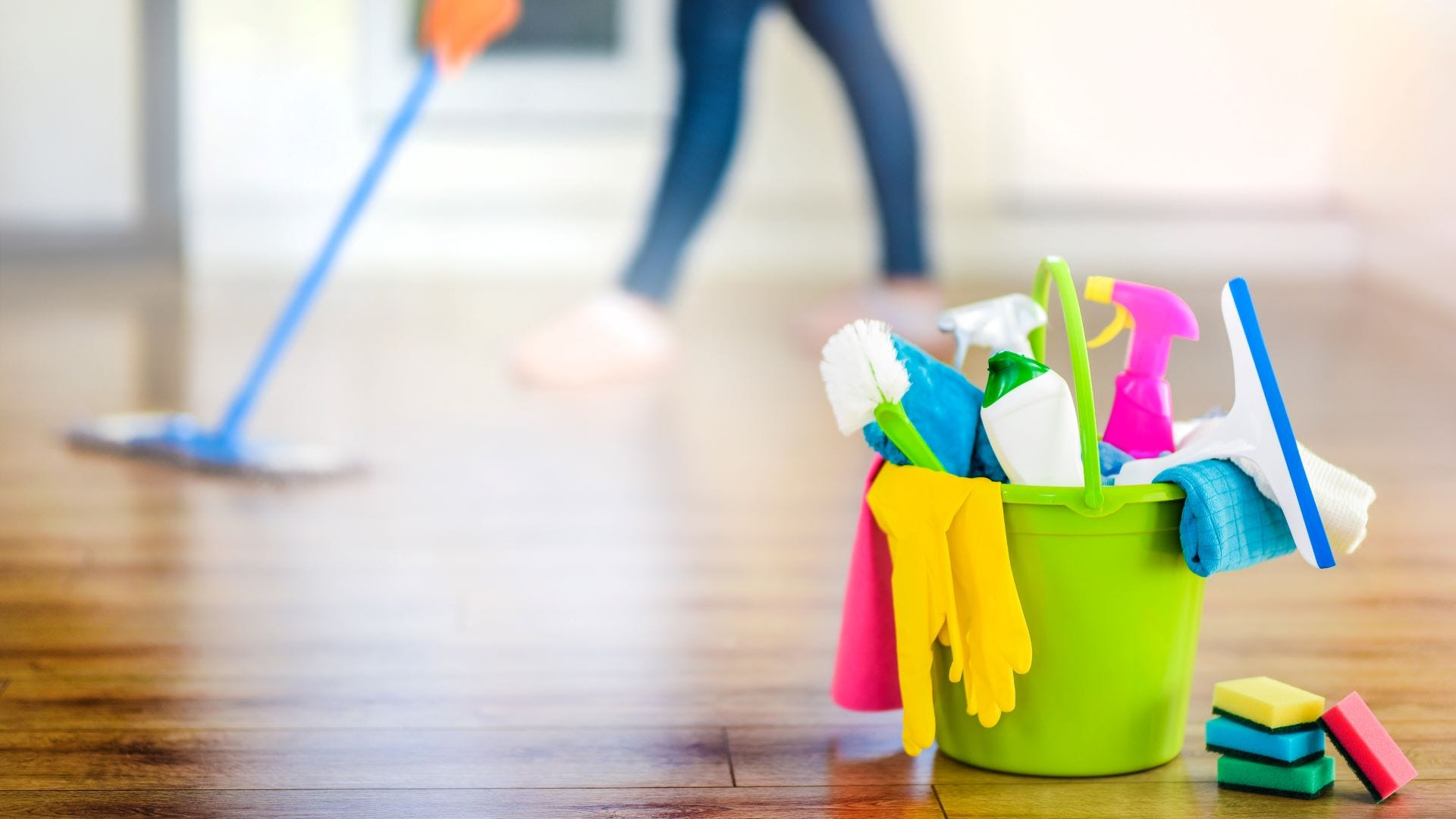 Cleaning supplies in a bucket with someone mopping in the background.