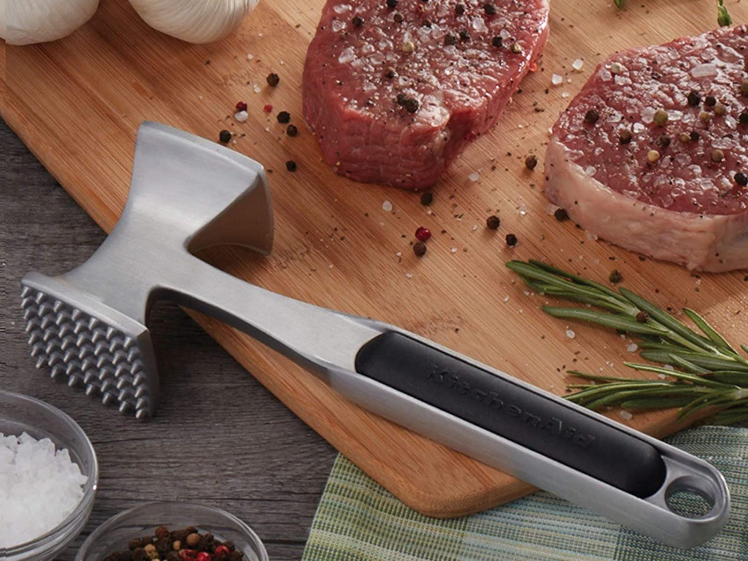 Silver hammer-shaped meat tenderizer sitting on a wood cutting board next to meat
