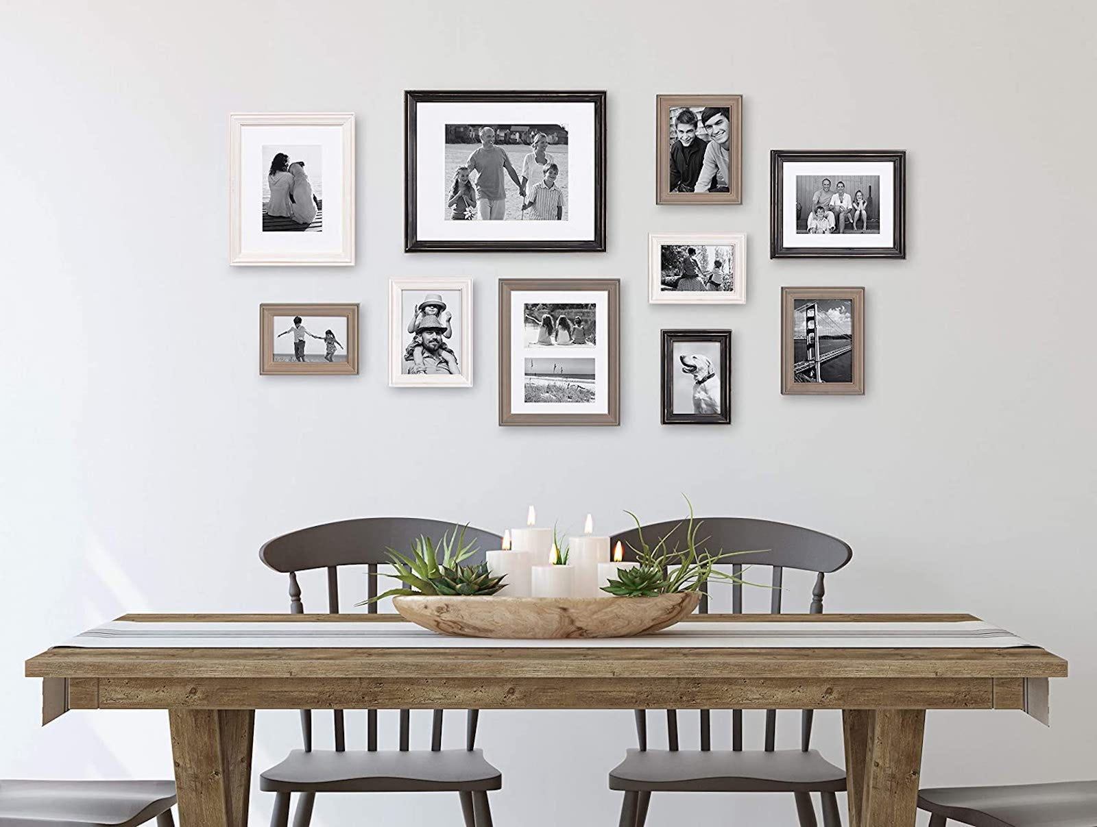 White wall in a dining room with several black-and-white photos in neutral-colored frames