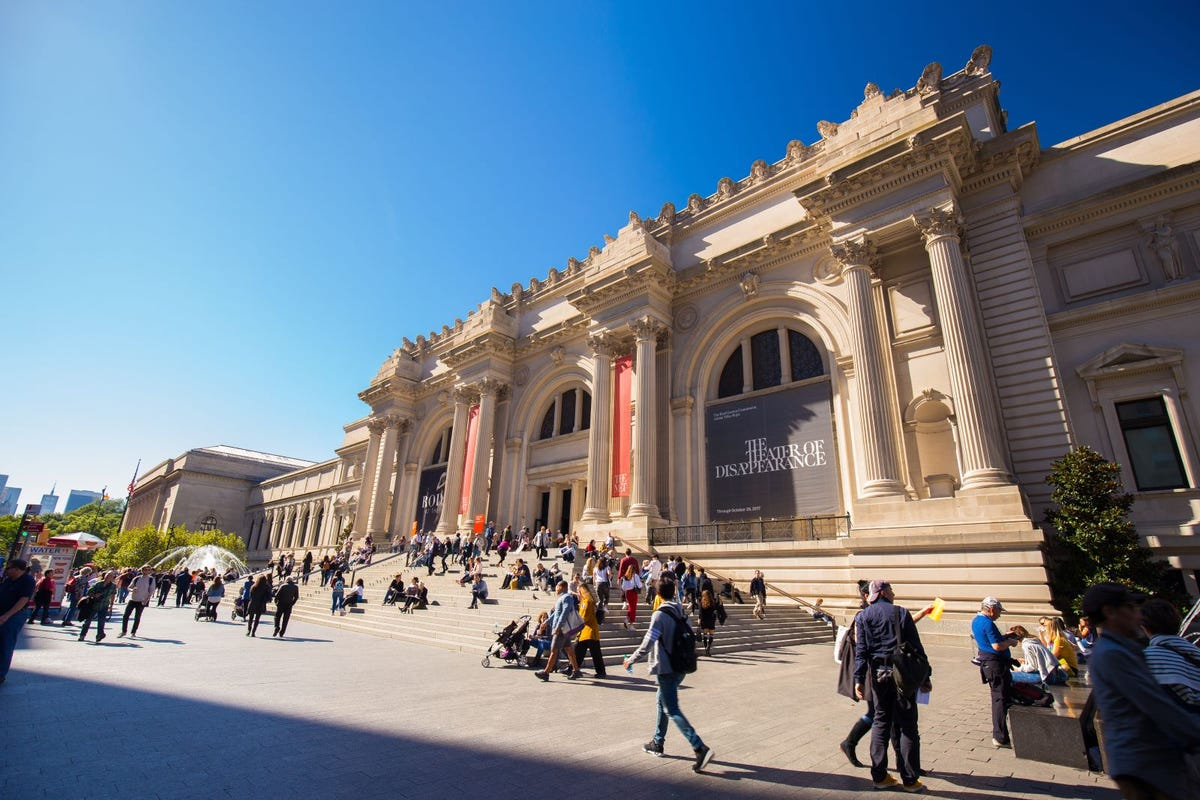 A crowd of visitors around the entrance of The Metropolitan Museum of Modern Art.