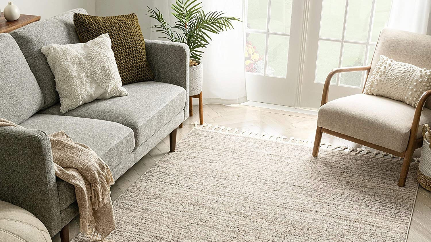 A living room with a beige rug and chair, and a gray sofa.