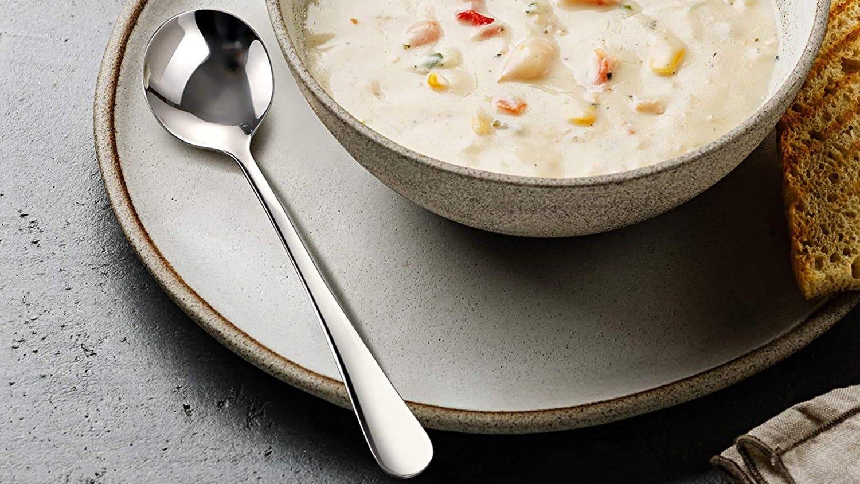 A soup spoon sitting next to a bowl of soup.
