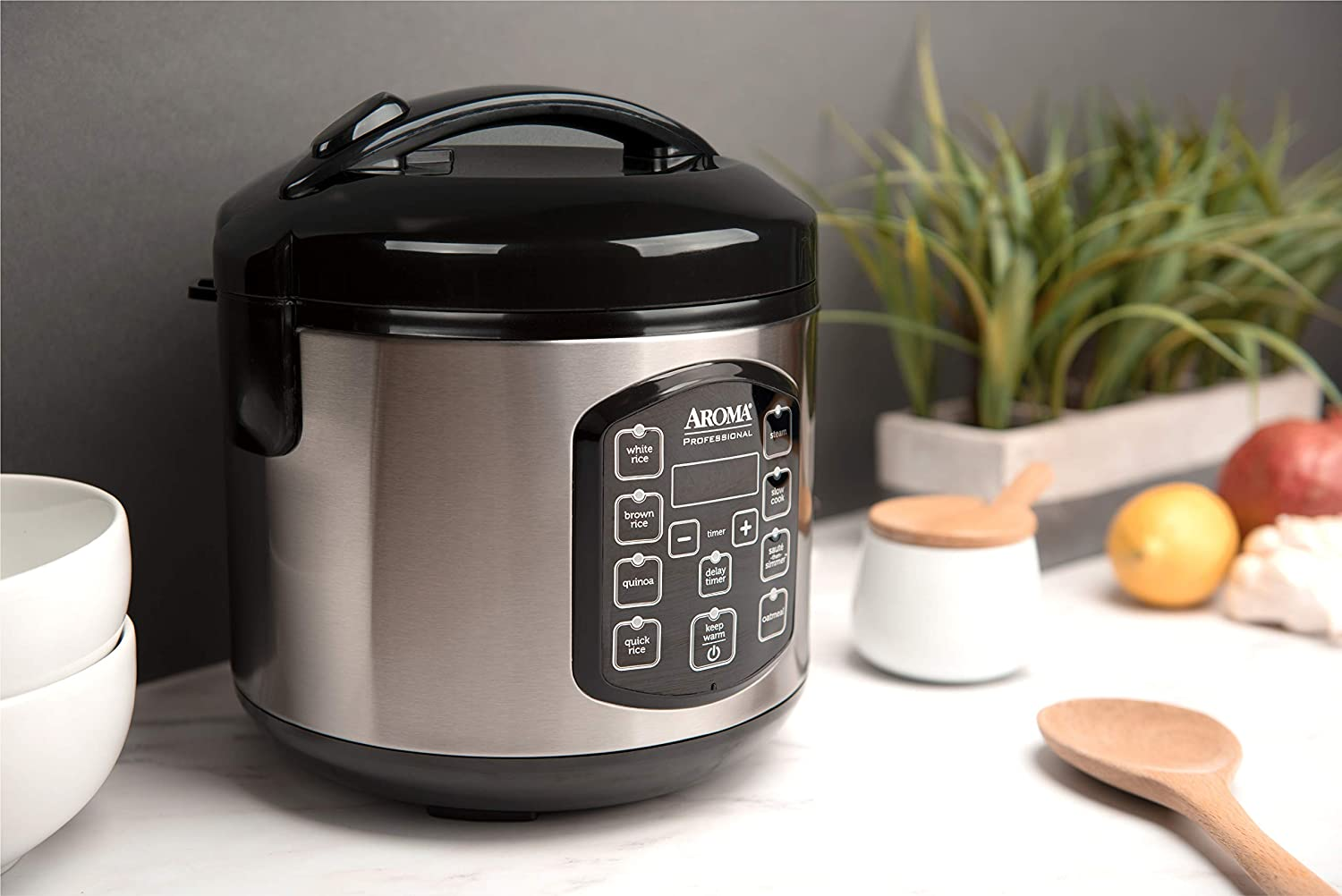 Silver and black rice cooker sitting on a white countertop