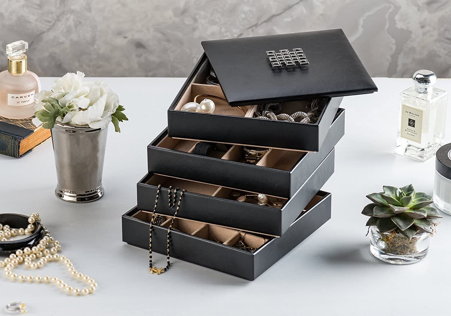 Four black, stackable jewelry cubbies stacked on top of each other