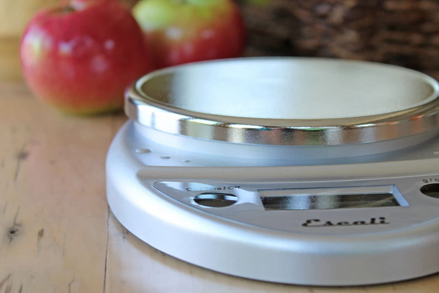 A white kitchen scale on a wood counter with apples in the background