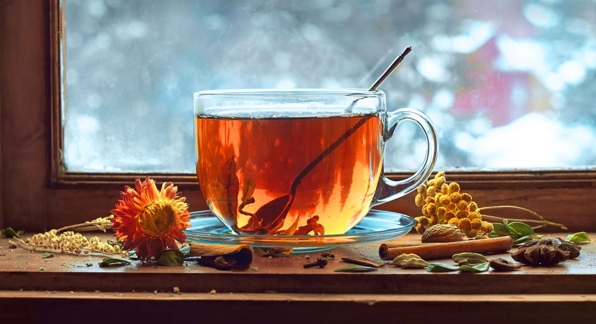 A glass mug of herbal tea sitting on a windowsill, surrounded by herbs and leaves.