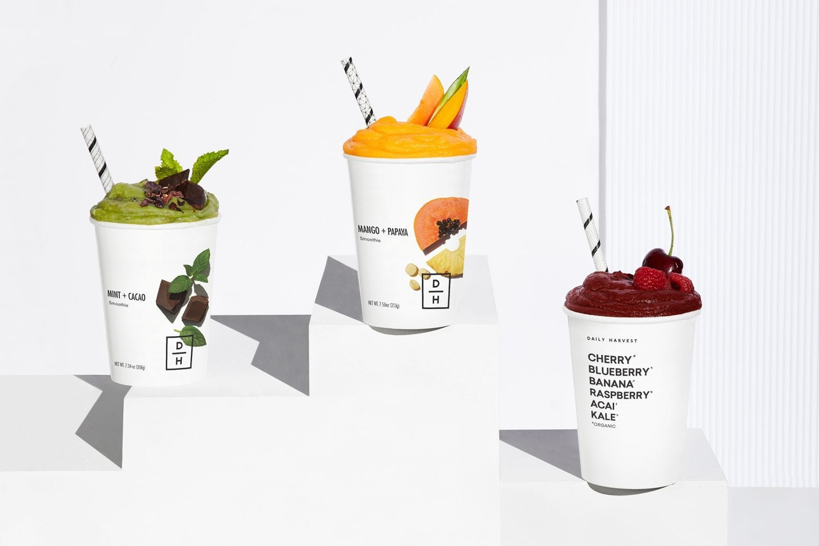 Three healthy and colorful smoothies on a white background.