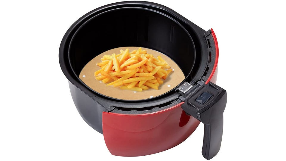 An air fryer with a parchment paper inside topped with golden french fries.