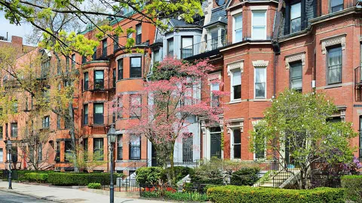 A row of brick townhomes is surrounded by greenery.