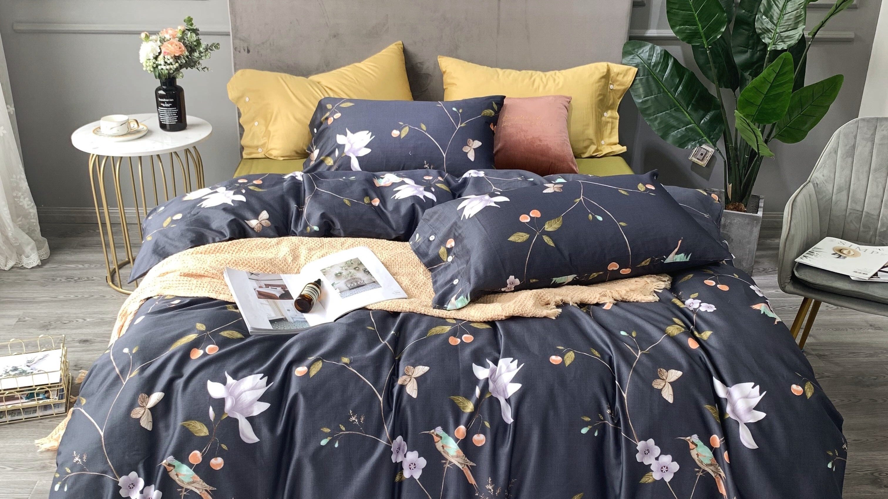 A dark-colored floral duvet and pillows on a bed.