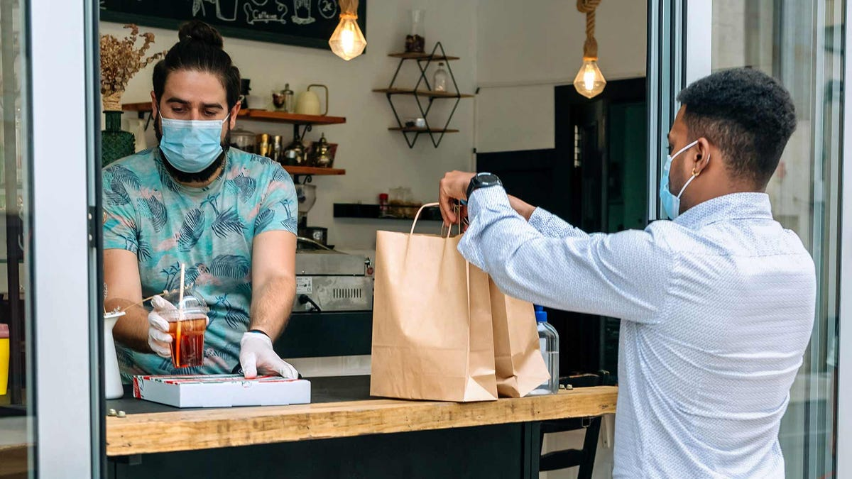 A young man picking up a take-away food order during the coronavirus pandemic.