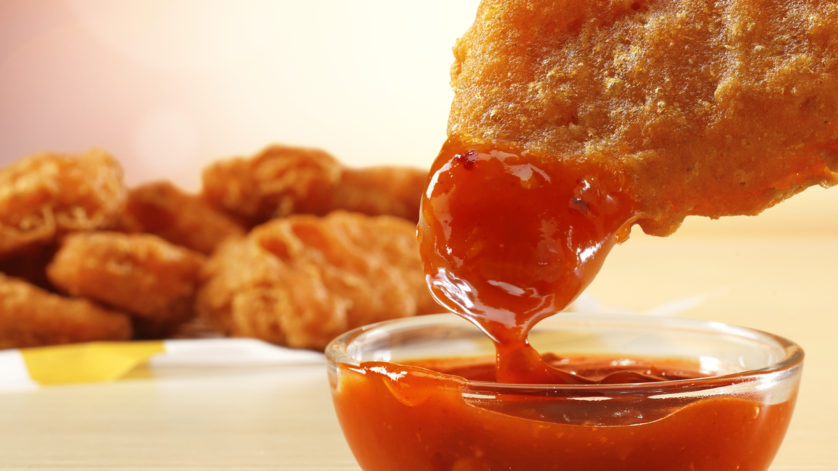 A spicy chicken McNugget being dipped in a bowl of sauce.