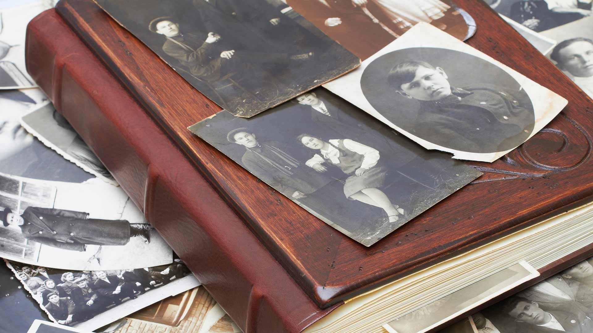An old family photo album with old photos sitting atop it.