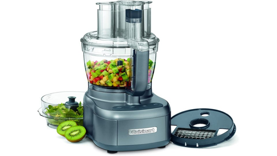 A Cuisinart food processor filled with fresh fruit with fresh kiwi on the side.