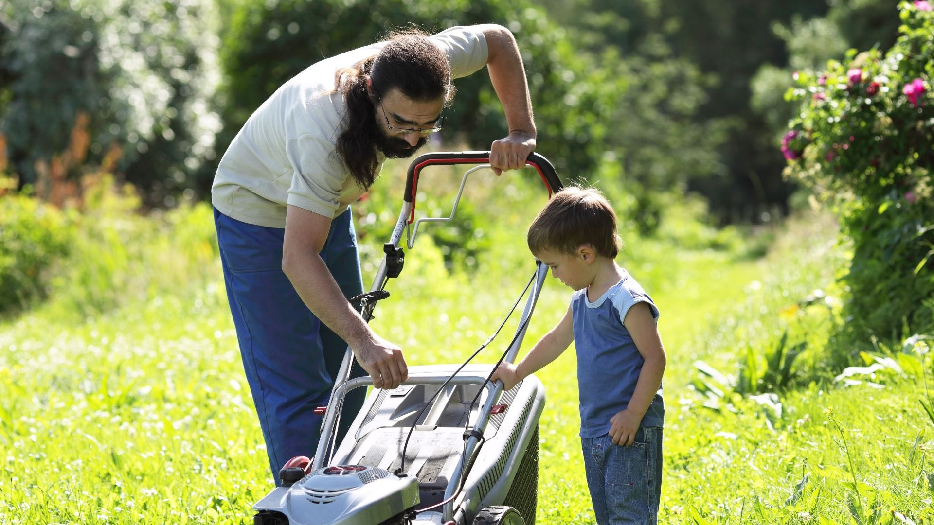 A man showing a little boy how to work a lawnmower.