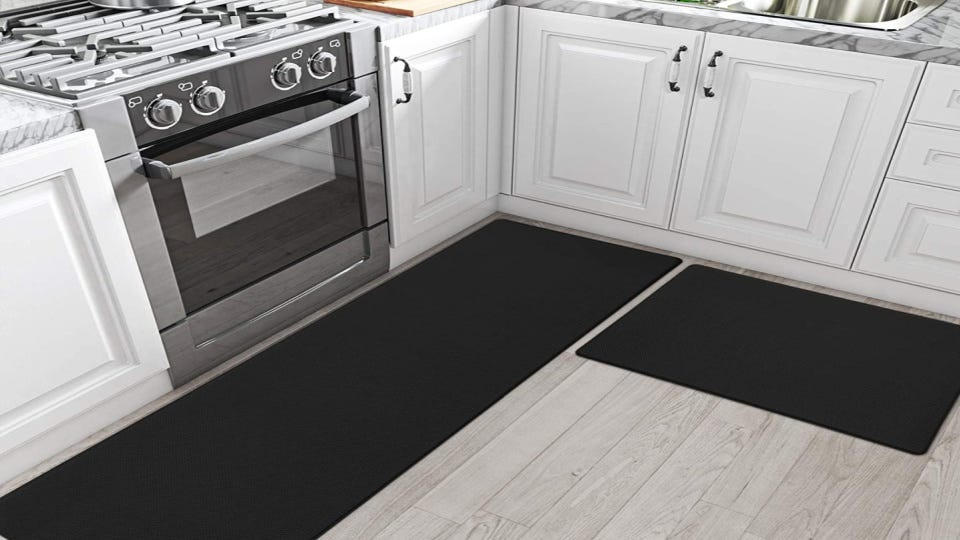 Two black DEXI anti-fatigue mats in a kitchen.