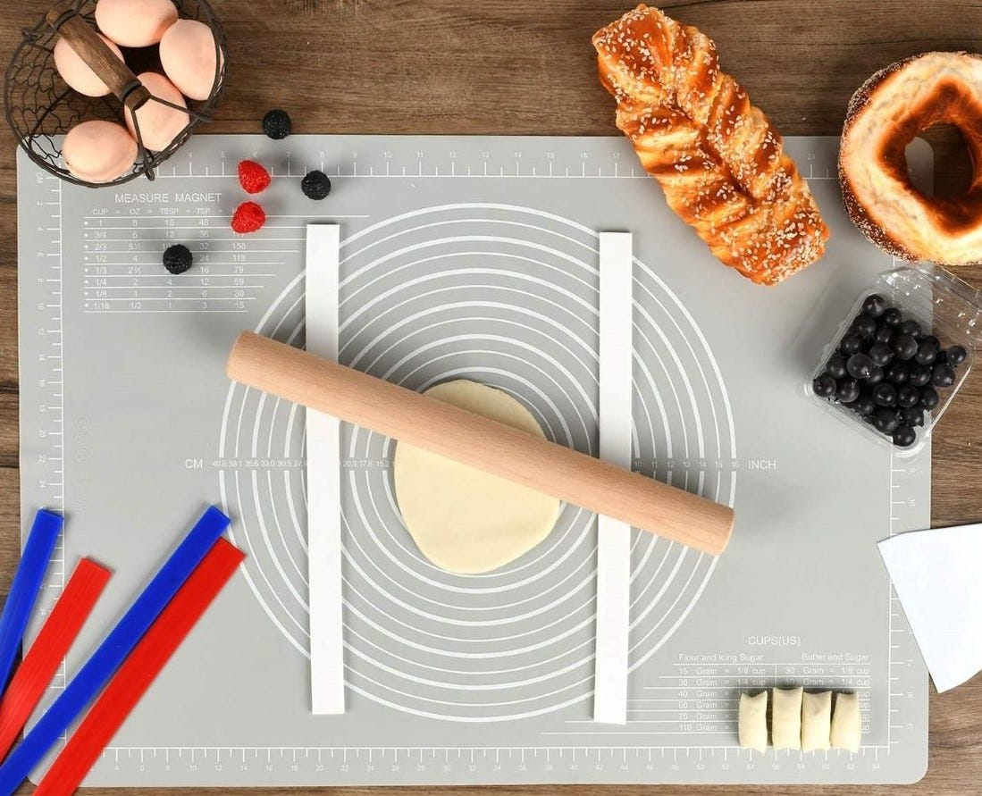 A non-slip silicone pastry mat on a counter surrounded by containers of food.